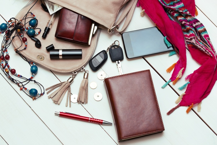 the contents of the female handbag - wallet, keys, phone, lipstick, perfume
